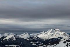 Berge bedeckt mit Schnee und durch Wolken umgeben lizenzfreie stockfotos