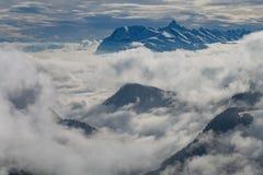 Berge bedeckt mit Schnee und Wolken und Bäume lizenzfreies stockbild
