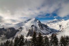 Berge bedeckt mit Schnee und Wolken und Bäume stockfoto