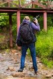 Berge de photographe de voyageur couverte de chemin d'herbe au pont en fer photo stock