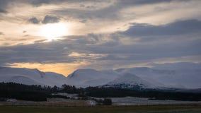 Berge des verschneiten Winters mit bewölkten Himmeln und Ackerland im Vordergrund Lizenzfreies Stockfoto