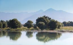 Berge durch den See und die Bäume stockfotos