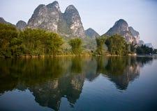 Berge durch Fluss Jadedragen durch Yangshuo Stockfotografie