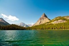 Berge durch Swiftcurrent Lake stockbilder