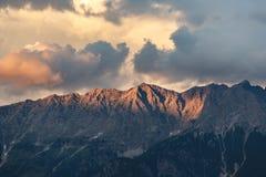 Berge entsteinen Spitzen mit orange Wolken unter Sonnenunterganglicht Stockfoto