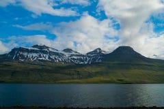Berge hinter einem kleinen Fluss Stockbilder