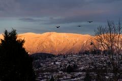 Berge im Schnee mit orange Licht vom Sonnenaufgang oder vom susnet Lizenzfreies Stockbild