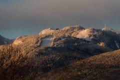 Berge im Schnee mit orange Licht vom Sonnenaufgang oder vom susnet Stockbild