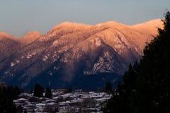 Berge im Schnee mit orange Licht vom Sonnenaufgang oder vom susnet Lizenzfreie Stockbilder