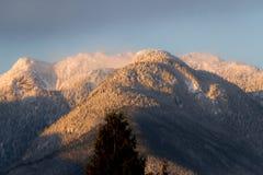 Berge im Schnee mit orange Licht vom Sonnenaufgang oder vom susnet Lizenzfreies Stockfoto