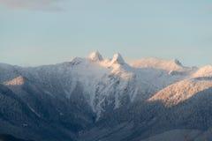 Berge im Schnee mit orange Licht vom Sonnenaufgang oder vom susnet Lizenzfreie Stockfotos