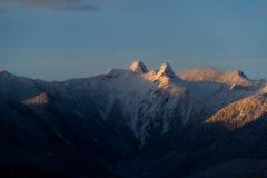 Berge im Schnee mit orange Licht vom Sonnenaufgang oder vom susnet Stockfotos