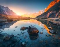 Berge mit belichteten Spitzen, Steine im Gebirgssee bei Sonnenuntergang Stockbild