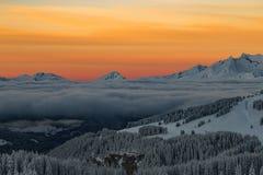 Berge mit einem Sonnenaufgang umgeben durch Wolken lizenzfreie stockfotos