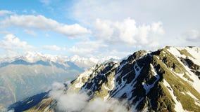 Berge mit Schnee-mit einer Kappe bedecktem blauem Himmel der Spitzen mit hellen Wolken Lizenzfreies Stockfoto