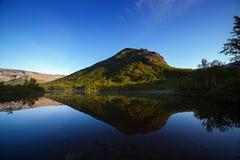Berge reflektierten sich in der glatten Oberfläche des Sees an der Dämmerung Stockfoto