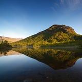 Berge reflektierten sich in der glatten Oberfläche des Sees an der Dämmerung Stockbild