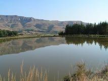 Berge reflektierten sich im ruhigen Wasser von einem See Lizenzfreies Stockfoto