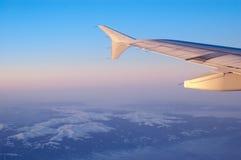 Berge und Flügel eines Flugzeuges Stockbilder