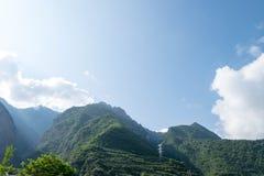 Berge und Hochspannungsbeitrag mit Strahl des Morgensonnenscheins Lizenzfreies Stockfoto