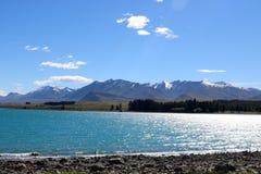 Berge und Licht auf Wasser, See Tekapo, NZ Stockfotos