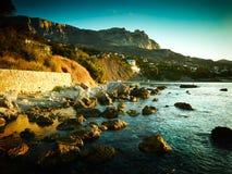 Berge und Meer bei Sonnenuntergang Blauer Himmel und blanke Hügel Stockfotografie