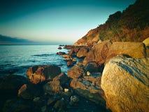 Berge und Meer bei Sonnenuntergang Blauer Himmel und blanke Hügel Lizenzfreies Stockfoto