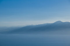 Berge und Meer im Nebel. Stockfotos