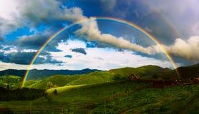Berge und Regenbogen stockbild