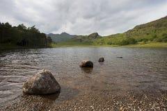 Berge und See am bewölkten Tag Stockfotos