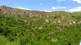 Berge von Armenien, Höhlenstadt von Khndzoresk in den Felsen, die in der grünen Vegetation ertrinken lizenzfreie stockfotografie