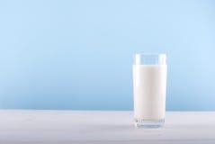Übergeben Sie auslaufende Milch von einem Krug in ein Glas Stockfoto