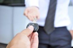 Übergeben Sie das Geben eines Autoschlüsselautoverkaufs- u. -mietservicekonzepts Stockfotografie