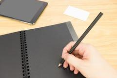 Übergeben Sie das Halten des Bleistiftschreibens auf leerem Schwarzbuch mit Tabelle und Visitenkarte Lizenzfreie Stockfotografie