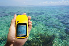 Übergeben Sie das Halten eines Marine-GPS-Navigators über dem Meer Stockbild