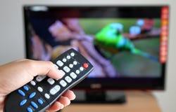 Übergeben Sie das Zeigen eines Fernsehapparates, der in Richtung zum Tele Fernsteuerungs ist Stockbild