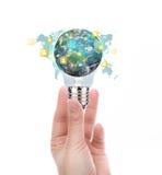 Übergeben Sie Griff Glühlampe mit Erde des Sozialen Netzes Stockfotos