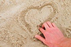 Übergeben Sie Herz des abgehobenen Betrages im Sand auf der Küste Stockfotos