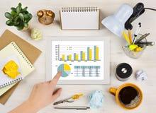 Übergeben Sie Schirm der rührenden Tablette mit Diagramm über Schreibtischhintergrund Lizenzfreies Stockfoto