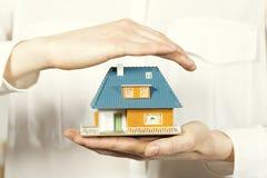Übergeben Sie schwebendes kleines Familienhaus, Hausversicherungskonzept Lizenzfreies Stockfoto