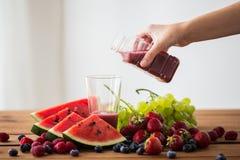 Übergeben Sie strömenden Fruchtsaft von Flasche zu Glas Stockfoto