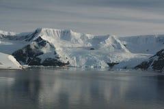 Bergen & gletsjers die in kalme oceaan worden weerspiegeld Stock Afbeeldingen