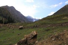 Bergen in de herfst met groen gras onder bewolkte hemel royalty-vrije stock afbeelding