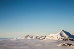 Bergen die met sneeuw worden behandeld en die door wolken worden omringd royalty-vrije stock foto