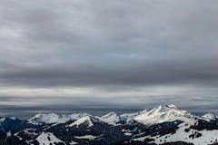 Bergen die met sneeuw worden behandeld en die door wolken worden omringd stock fotografie