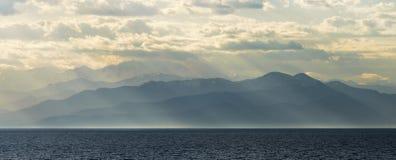 Bergen door het overzees in zon Stock Foto's