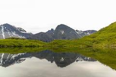 Bergen door Meer worden weerspiegeld dat Royalty-vrije Stock Fotografie