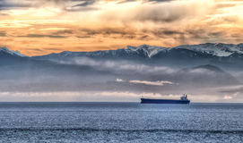 Bergen en Oranje Hemel met Één Schip van het Vervoer Royalty-vrije Stock Afbeeldingen