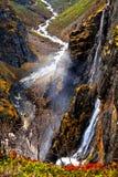 Bergen en stroom die van water van een rots in de vallei stromen, Stock Afbeelding