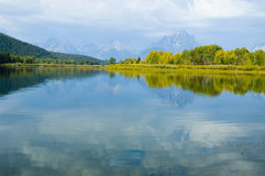 Bergen, hemel en dalingskleuren die in meer worden weerspiegeld stock foto